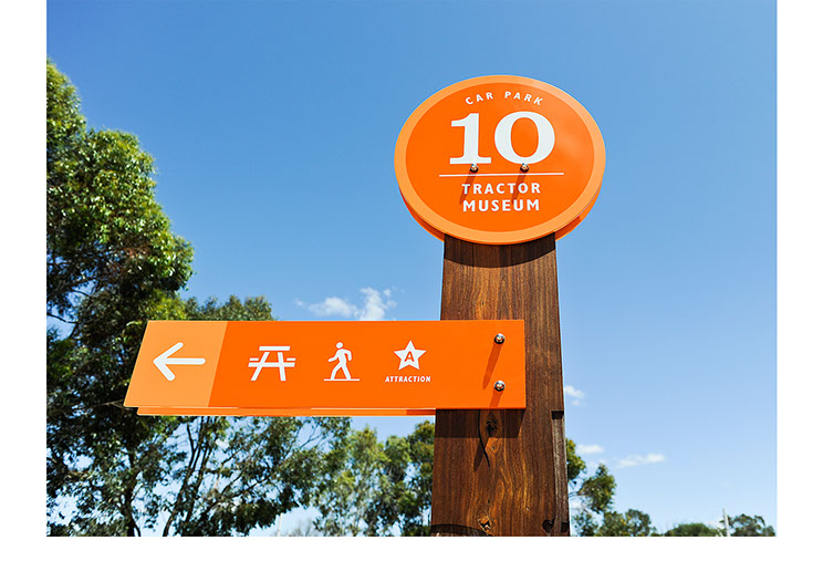 Outside signs design Whiteman Park. Location 10 close-up top of car park sign with arrows and icons pointing to  locations by Dessein, Australia